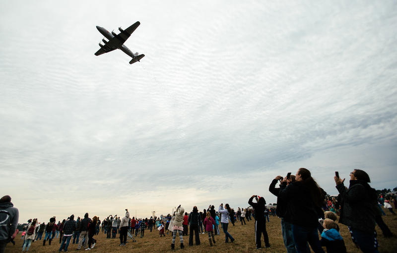 A World War II era aircraft drops candy to children below as it flies over Dare County Regional Airport in Manteo, N.C. on Sunday, Dec. 17, 2017.