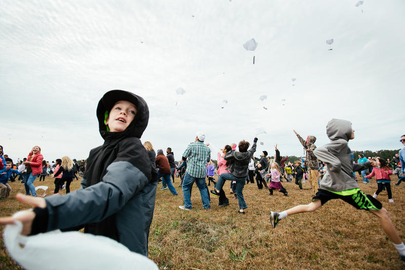 Children scramble to catch candy attatched to parachutes and dropped from a World War II era aircraft during an event in Manteo, N.C. on Sunday, Dec. 17, 2017.