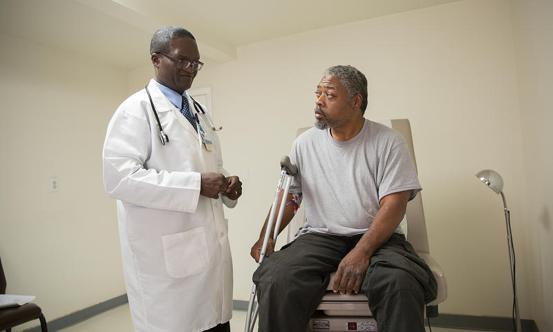 of Dr. Francis Aniekwensi visits with patient Calvin Elps. Aniekwensi is currently one of two part-time physicians in Warren County. He welcomes the news of a new doctor in town.