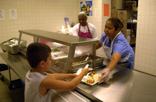 Two servers hand a tray of food to child in school cafeteria.