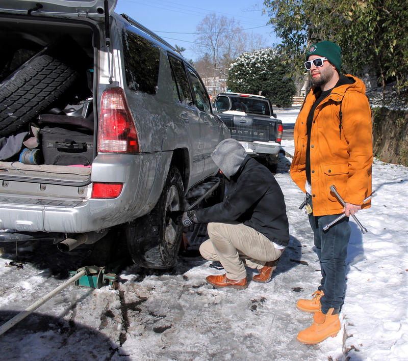 Brandon Lemasters, standing, helps a friend change a tire on his SUV on Thursday, Jan. 18, 2018, in Winston-Salem, after the vehicle slid through a curve on a ice-covered street the day before and hit a curb.