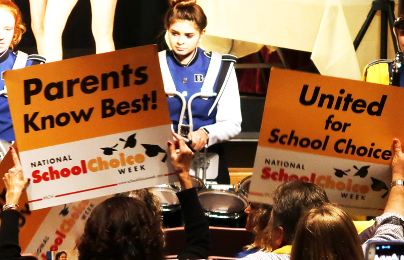 Parents wave National School Choice Week banners at rally in North Carolina Museum of History in Raleigh.