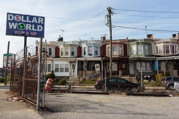 photo of a rundown looking row of houses with a 'dollar world' sign in the foreground