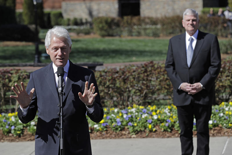 Former President Bill Clinton, left, speaks to the media as Franklin Graham, right, listens after paying respects to Rev. Billy Graham during a public viewing at the Billy Graham Library in Charlotte, N.C., Tuesday, Feb. 27, 2018.