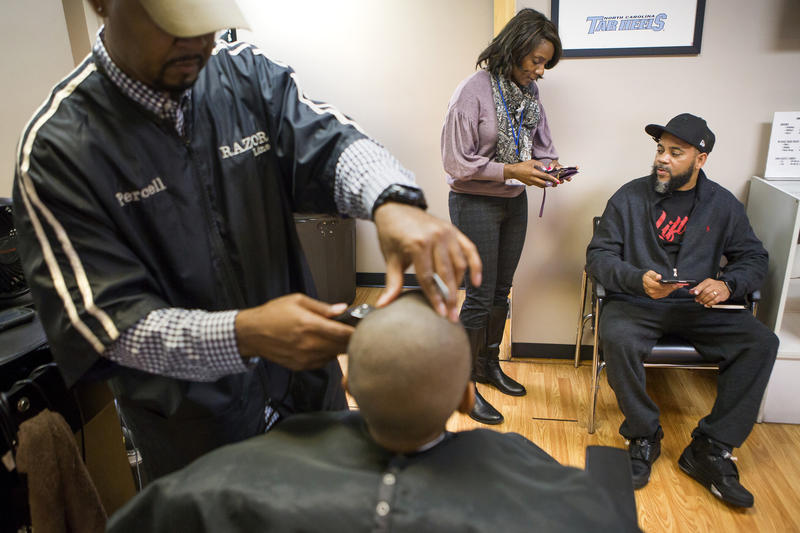 Dr. Tanya Coakley, center right, talks with Brad Huff, right, about a study she's conducting while Brad's son Drew Huff, 10, gets his hair cut by Percell McCain owner of Razor Line Barbershop in Greensboro on Saturday, February 17, 2018. Dr. Coakley, a pr