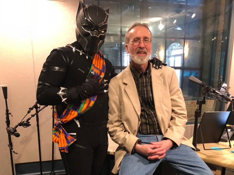photo of Victor Lawe dressed as  the black panther in the studio with host Frank Stasio