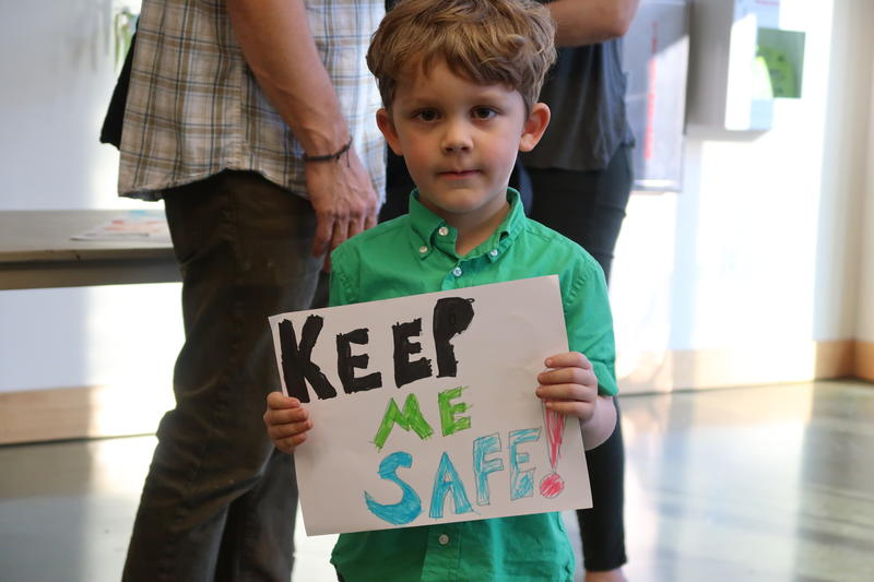 boy holds gun control sign