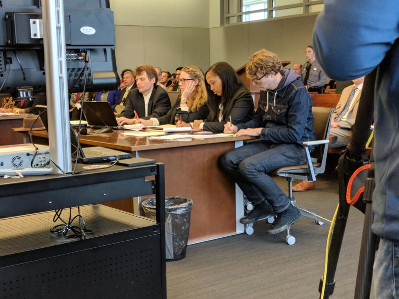 Dante Strobino (at right in jean jacket) takes notes during his trial on Monday, Feb. 19, 2018. Strobino is one of eight people facing charges for toppling a Confederate Monument in downtown Durham last summer.