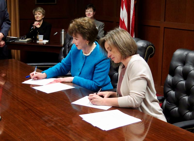 Two university leaders signing an agreement at a wooden table