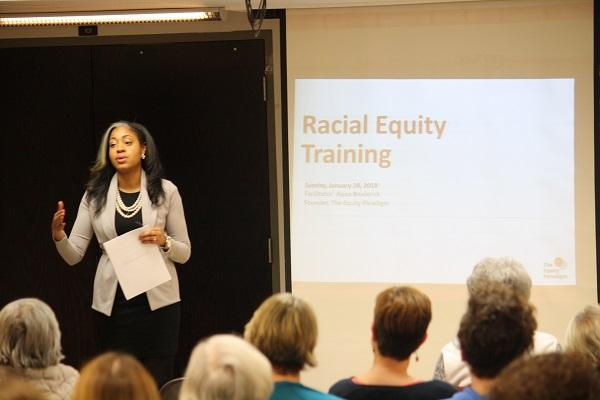 Photo of Broderick presenting to a room of people, 'racial equity training' is projected onto wall