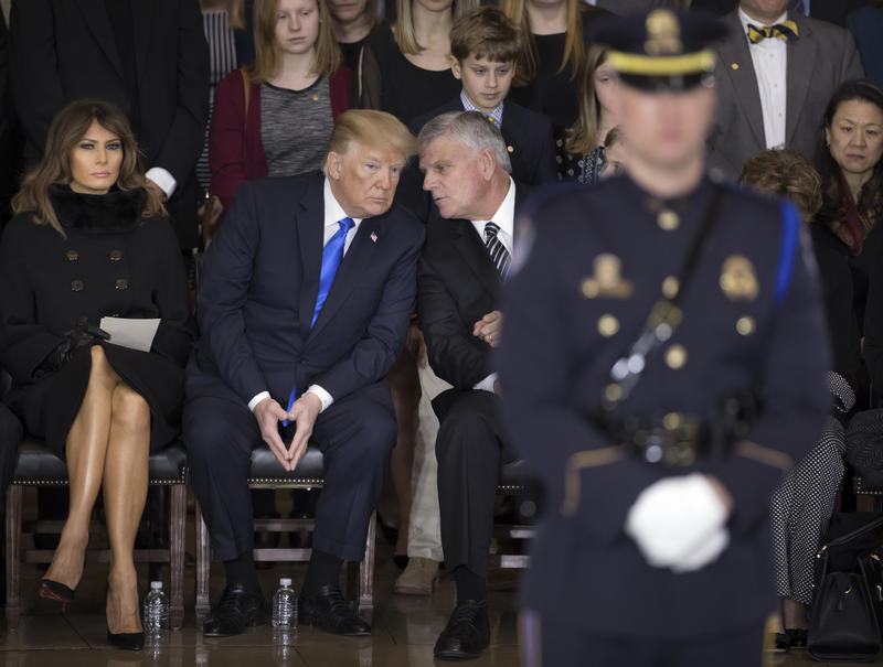 President Donald Trump, joined at left by first lady Melania Trump, speaks with Rev. Billy Graham's son, Rev. Franklin Graham, right, as America's most famous evangelist lies in honor in the Capitol Rotunda, Feb. 28.