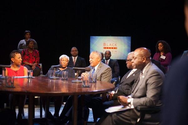 photo of a round table discussion, 'Black Issues Forum' banner in the background