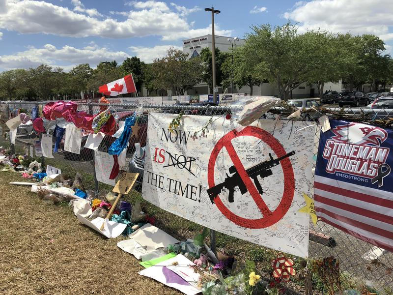 Memorial and calls for gun control cover a fence outside of Marjory Stoneman Douglas High in Parkland, Florida.