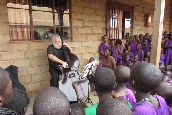 photo of Dobbs playing the double bass for a group of children