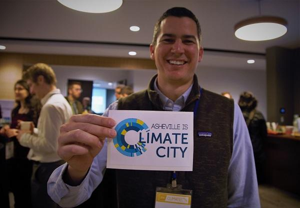 photo of a man holding a card that says 'asheville is climate city'
