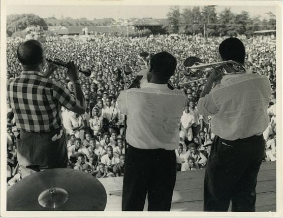 photo of three men playing horns for a huge crowd