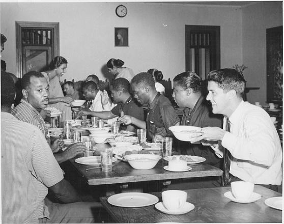photo of people seated at a long table eating a meal