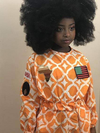 photo of a young girl in an orange astronaut's jumpsuit