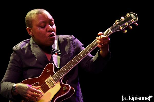 photo of meshell ndegeocello playing guitar onstage
