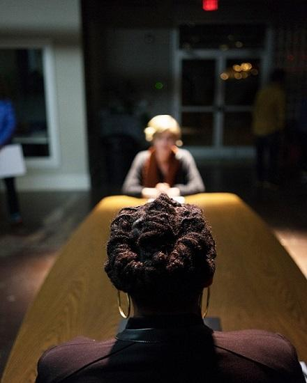photo of the back of an african american woman's head, facing a white woman across a table who is out of focus