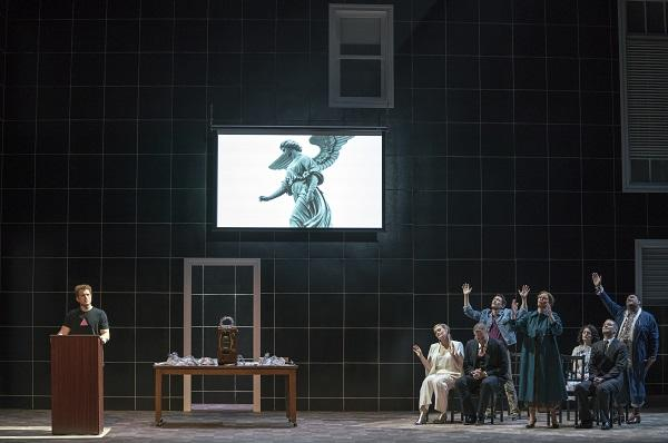 photo of stage production - a man speaks at a podium and a group of people look up at an angel figure
