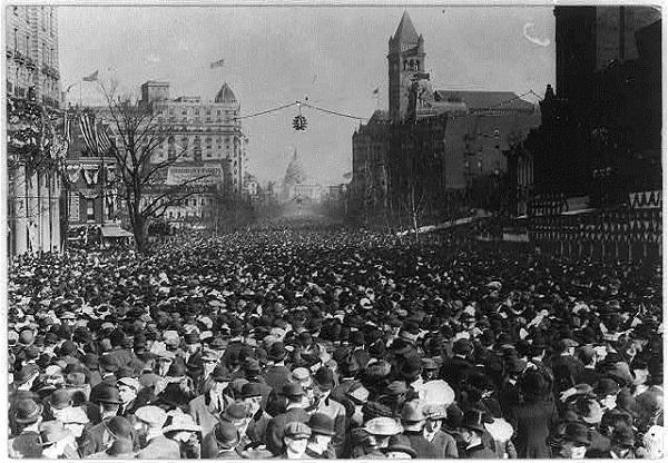 photo of streets packed full of people, the US capitol building in the distance