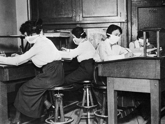 photo of several women working at desks, wearing mouth-covering masks