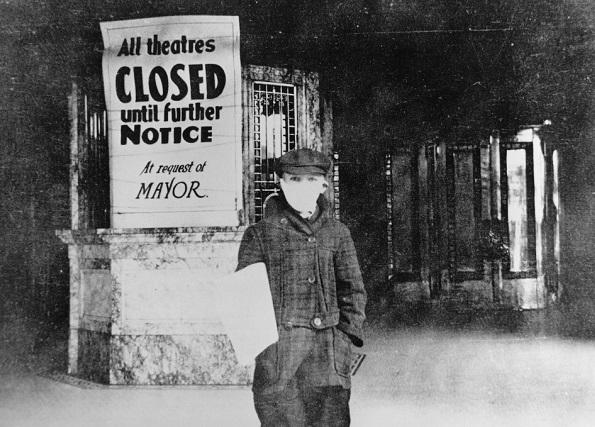 photo of a young person in a mouth-covering mask in front of a closed theater. the sign says 'all theatres closed until further notice at request of mayor.'