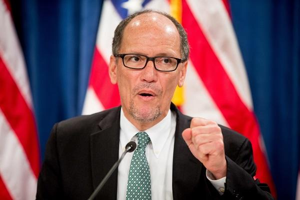 photo of tom perez speaking at a microphone, an american flag in the background
