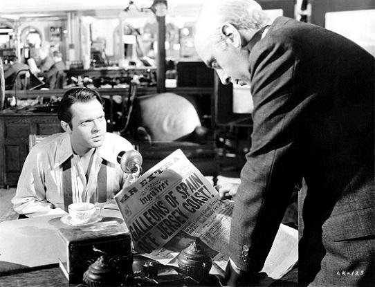 still photo from the film, picturing welles seated at a table and coulouris gesturing with a newspaper