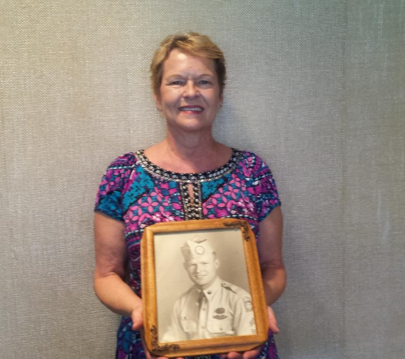Debbie Crain holds a portrait of her father, Lonnie Sanders, taken during World War II.