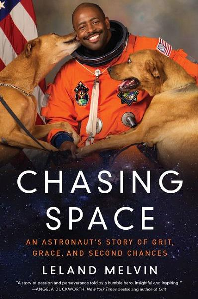 book cover for 'chasing space.' leland melvin poses for an official portrait in astronaut's gear, but with two big dogs licking his face.