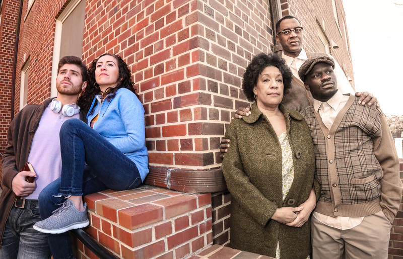 Actors Carlos Alcala, Sarita Ocón, Kathryn Hunter-Williams, Samuel Ray Gates, and Alex Givens pose by a brick wall in a promo picture for the play 'Leaving Eden'