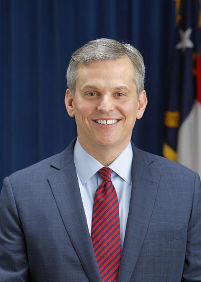 headshot of Josh Stein, NC flag in the background