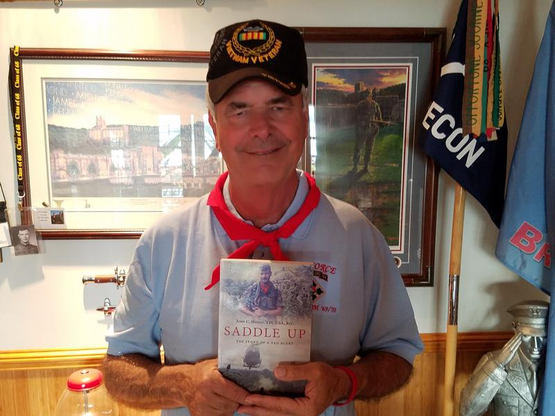 photo of John Hedley holding his book Saddle Up.