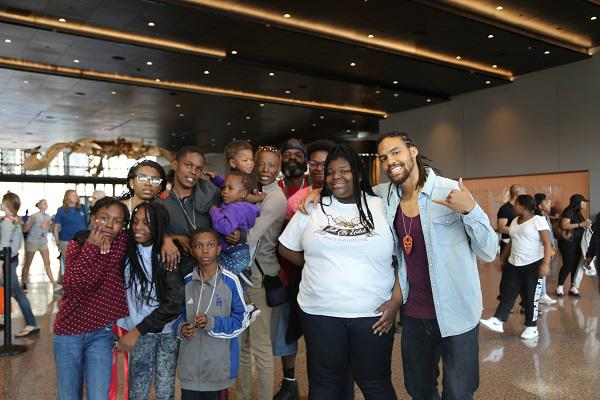 photo of freelon and a group of students and families in the museum lobby