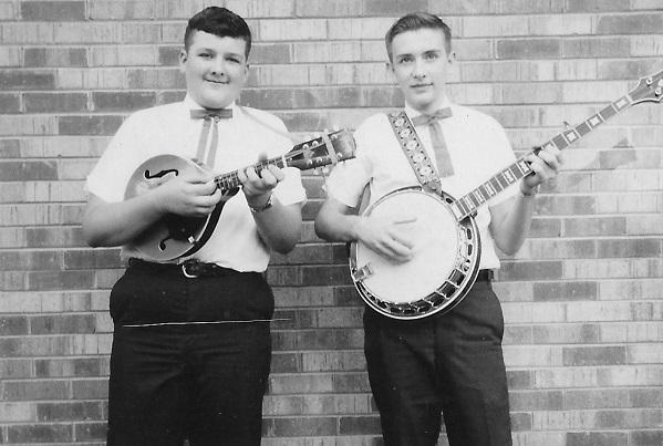 photo of two boys in the teens holding a mandolin and banjo