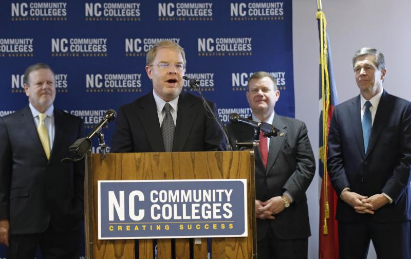 Peter Hans, the newly elected president of the N.C. Community College System, delivers remarks while North Carolina Senate President Pro Tempore Phil Berger, from left, House Speaker Tim Moore and Gov. Roy Cooper listen during a news conference in Raleigh