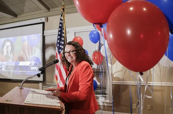 photo of eastman amongst red and blue baloons, speaking at a podium