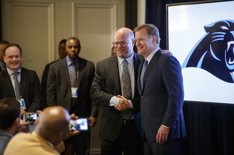 New Carolina Panthers owner David Tepper, left, shakes hands with NFL Commissioner Roger Goodell