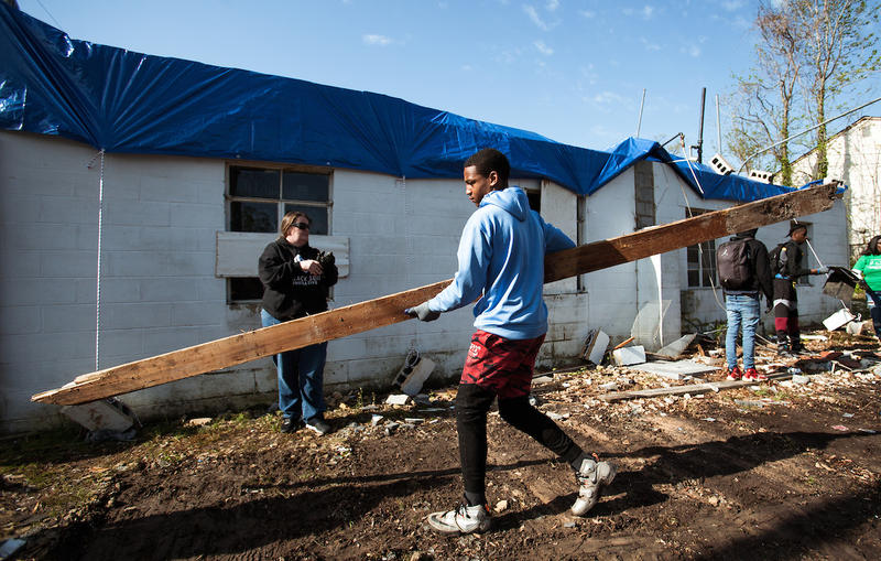 Tahj Turner helps clear debris from a tornado-damaged site while working with the Black Suits Initiative in Greensboro
