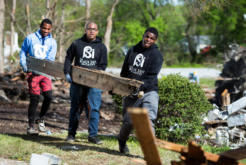 D'wann Harvin-Bailey, right, Christopher Foust, middle, and Tahj Turner, left, help clear debris from a tornado-damaged site while working with the Black Suits Initiative in Greensboro, N.C. on Saturday, April 28, 2018.