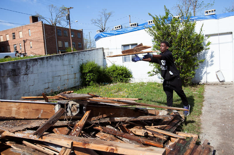 Le-Quan Robinson helps clear debris from a tornado-damaged site while working with the Black Suits Initiative in Greensboro