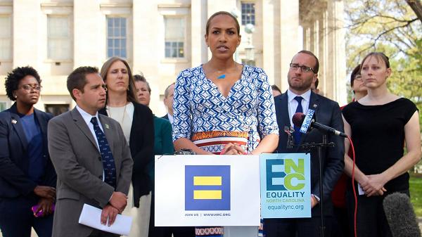photo of Candis Cox speaking at a podium with signs for the human rights campaign and equality NC