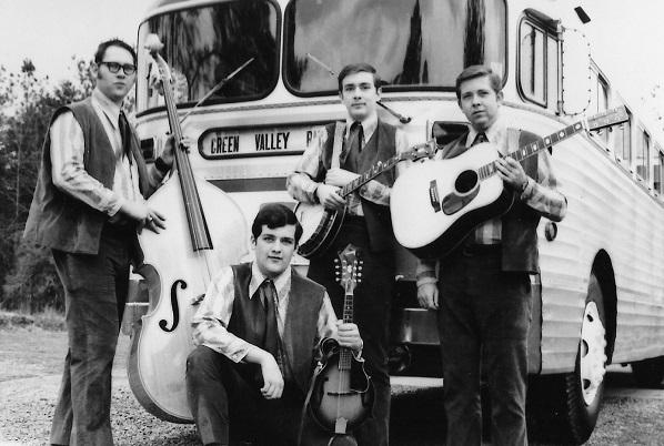 photo of 4 young adults posing in front of a touring bus with instruments