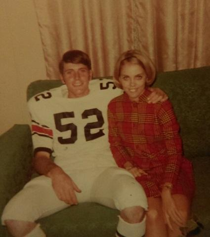 faded photo of mcbane and mann, smiling and seated on a couch