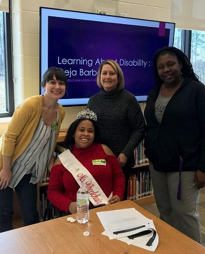 photo of four women in a classroom. one of the women wears a 'ms. wheelchair nc' sash.