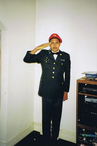 photo of cox as a teenager, dressed in rotc uniform and saluting. before transition.