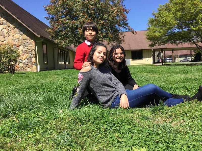 From left to right, Eddie, Natalie and Maria Fernanda Cortes, seated outside Mount Pisgah Academy, a private Seventh-Day Adventist academy near Asheville, where the two sisters will attend school in Fall 2018.