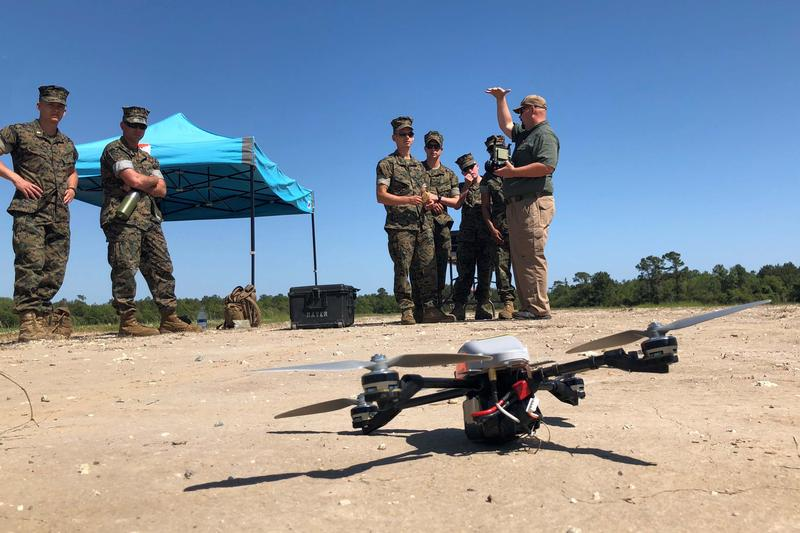 Civilian contractor Terry Pullum of Evolving Resources Inc. gives young Marines their first hands-on lesson in flying the InstantEye quadcopter.